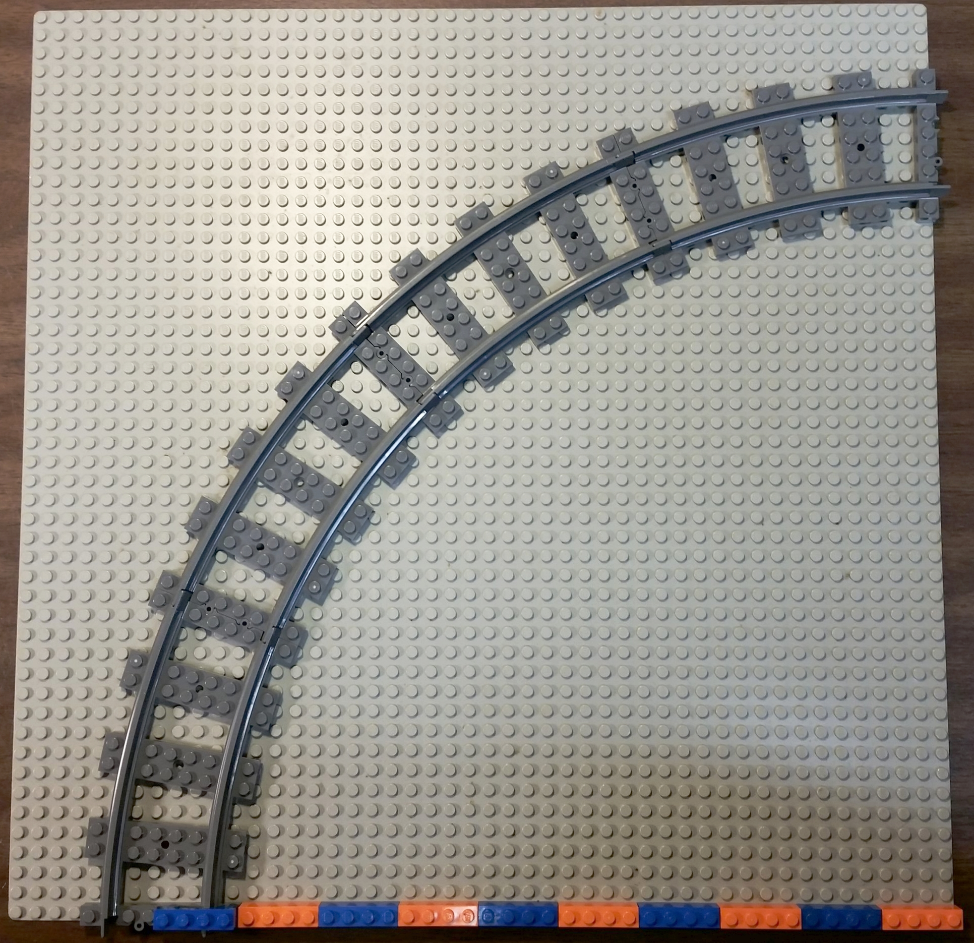 The distance from the center of the circle of track to the center of the rails is 40 studs, measured by the orange and blue 4-stud long bricks.
