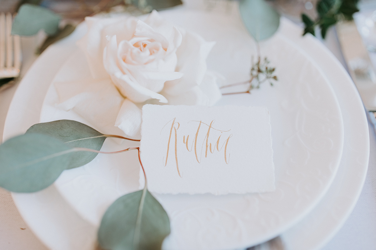 Winter wedding with greenery details and calligraphy by Sydney Beth Designs. Photo by Alex Lasota