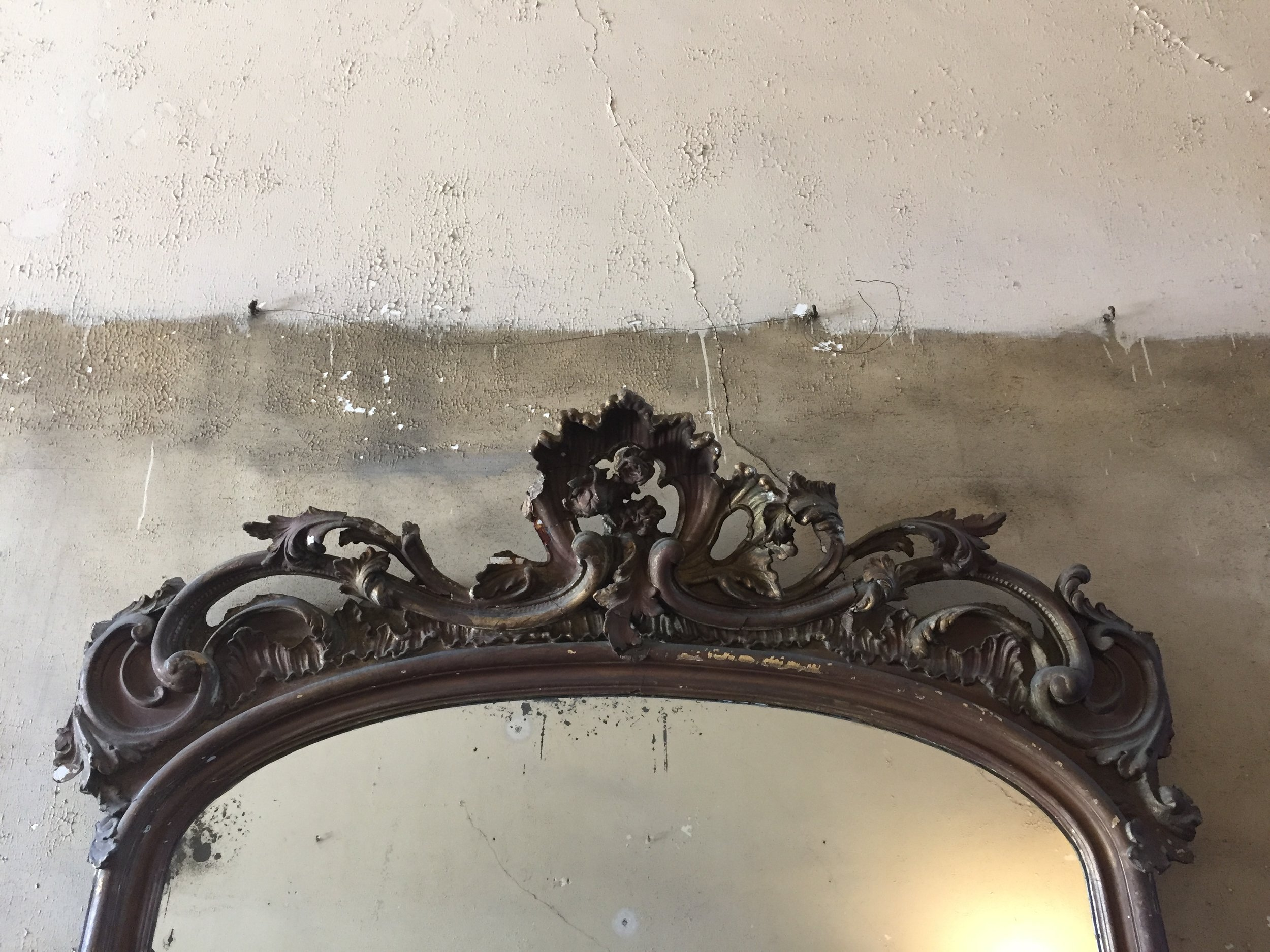 """The furniture and decor in the house are original to the families who lived there. It is clear that time has left its mark. There is still something so beautiful about the scroll work and """"C"""" - curves that go into this floor mirror spanning the second floor hallway as shown above."""