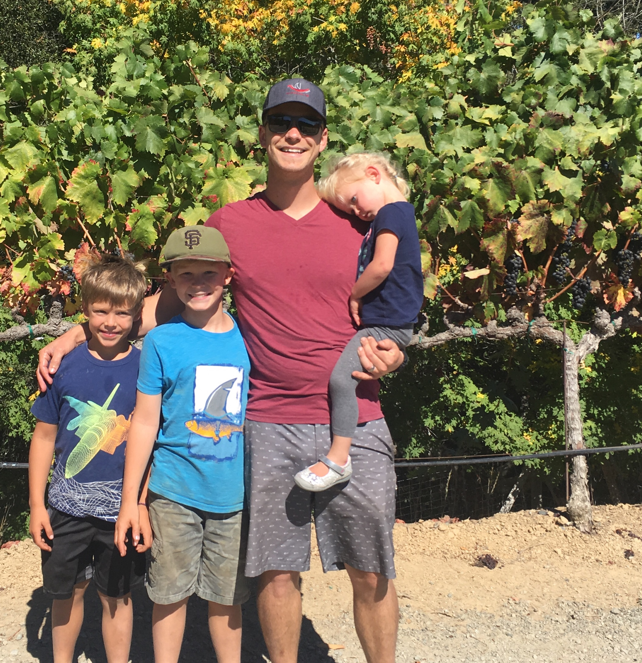 Adobe Road Winemaker Garrett Martin and his kids among the Zinfandel at Famighetti Vineyards.