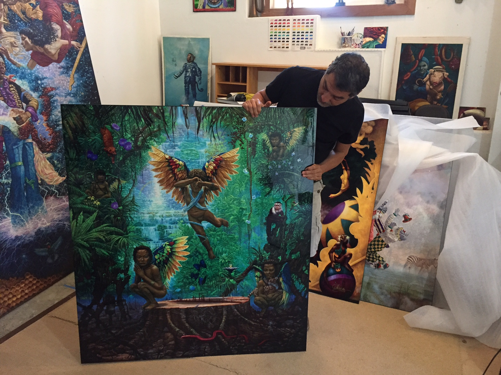 "Artist in his studio  with the metal print ""Feral Angels"""
