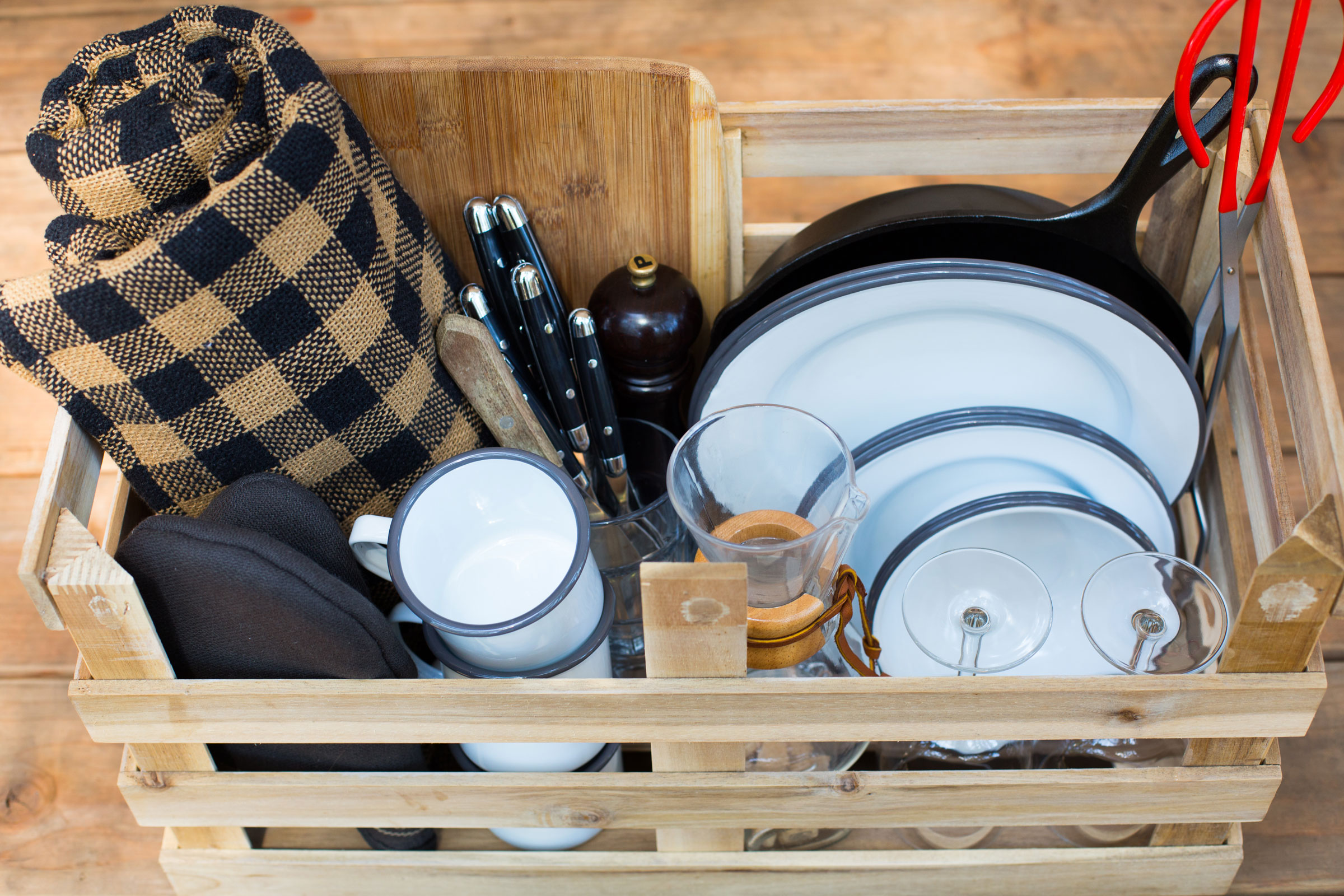 a crate with picnic essentials — metal camping plates and mugs, camping utensils, wine glasses, blanket, pan and more