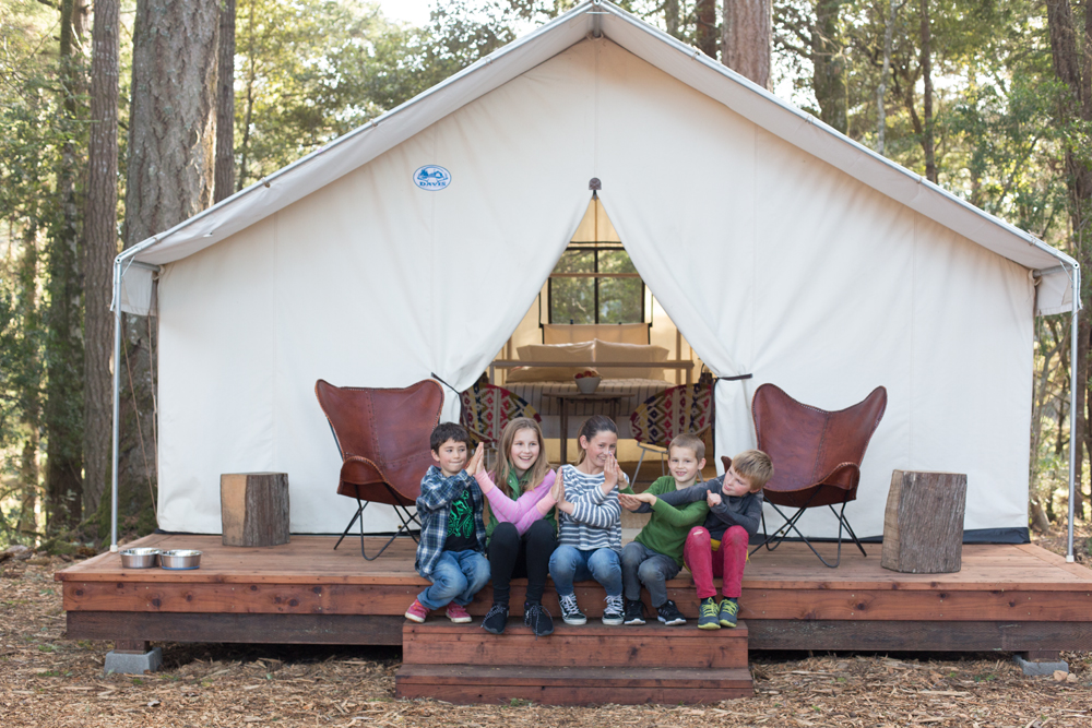 A family sits on the steps of the deck of a family tent