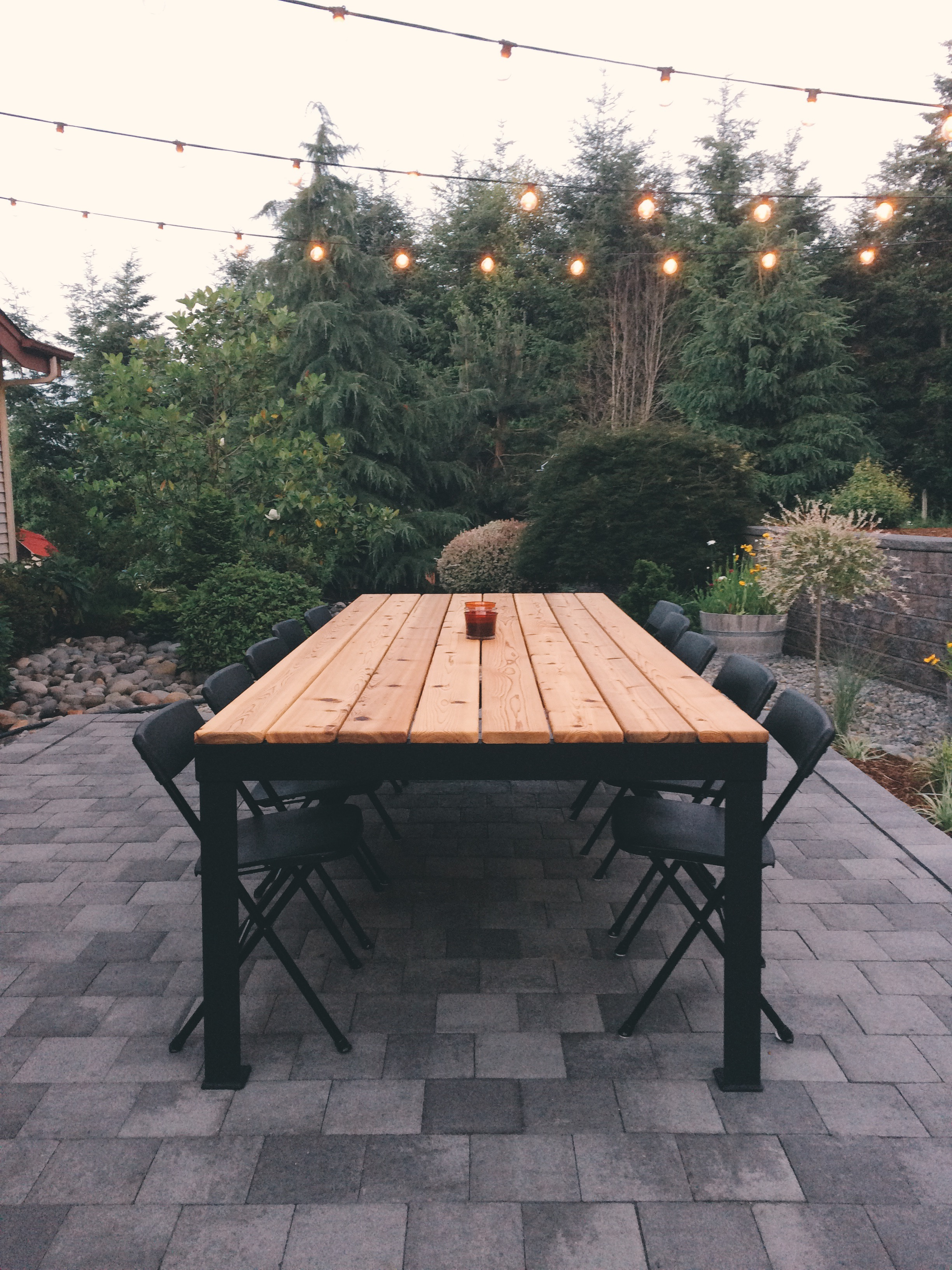 An outdoor dining room has a ten foot long, custom designed steel and wood table as its centerpiece.