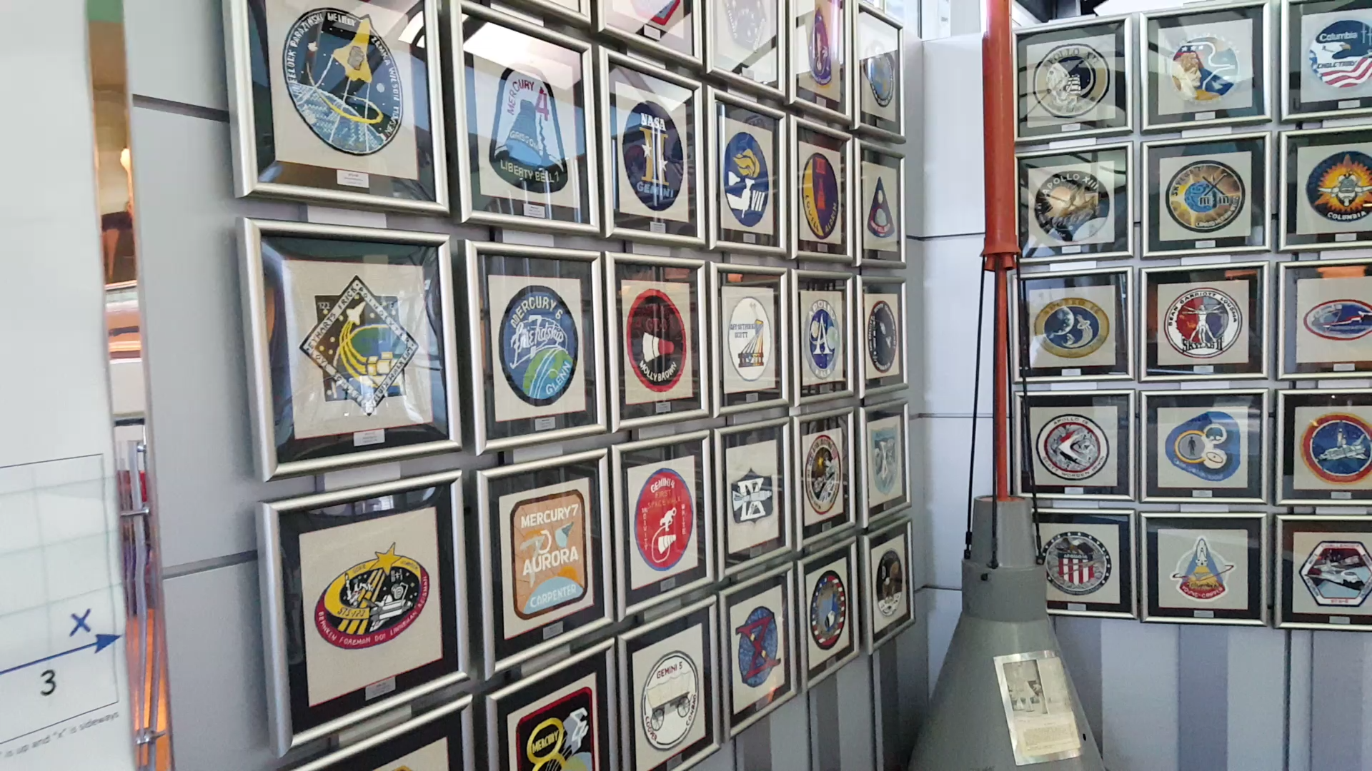 The wall of patches stretches on and on with a patch from every space mission, framed and hung in a row