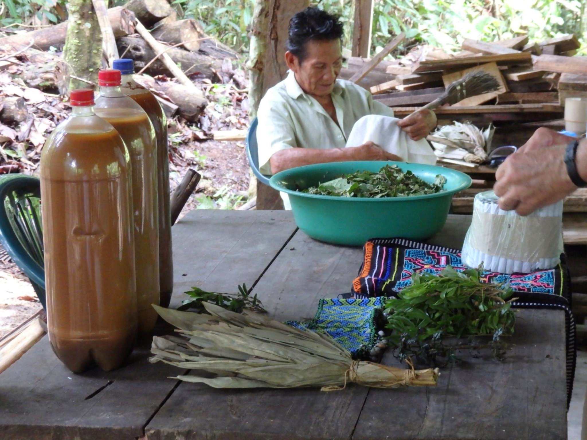 The Ayahuasca brew, chakapa (bundle of dried leaves), shipibo artwork, mapacho cigarettes & chacruna leaves. Don Rober sits in the background. Photo: Melanie Crandall