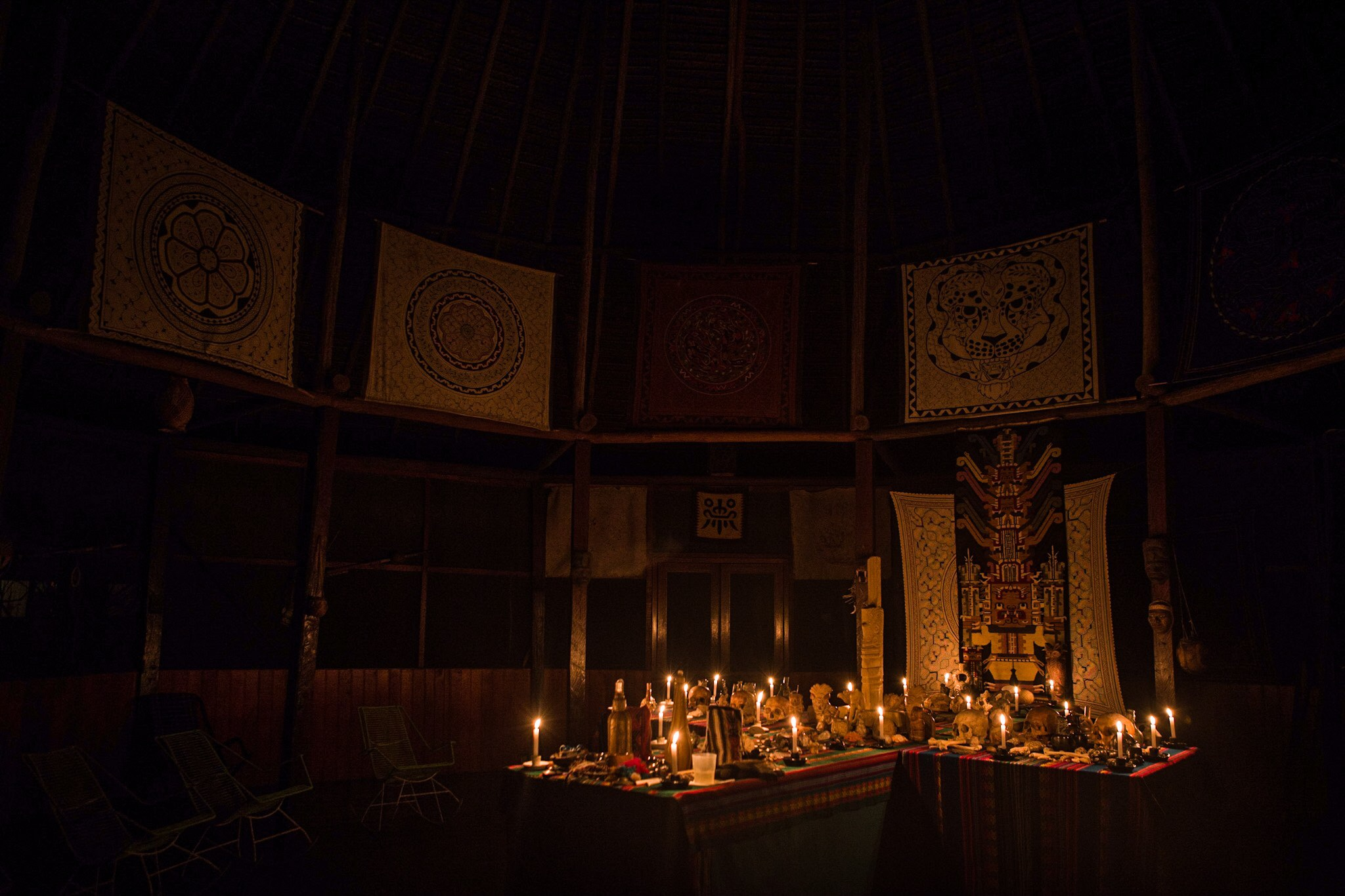 The hauntingly beautiful Huachuma mesa. Note the jaguar tapestry above, the Huachuma warrior holding the two cacti below, and the human skulls on the alter. Photo: Darin Basile