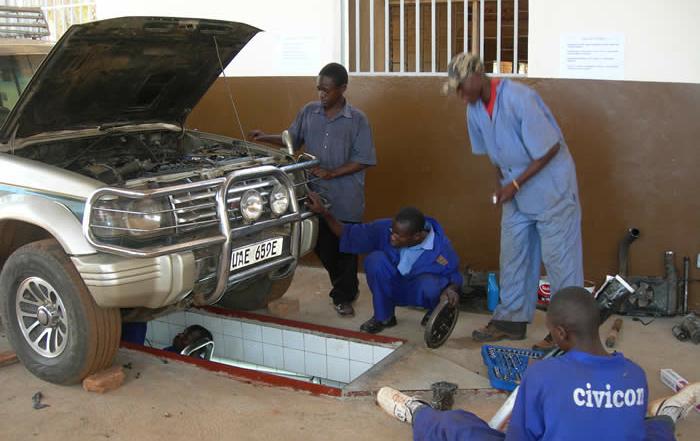 Motor vehicle mecanics students at work