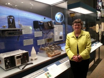 Caption: Dr. Alison Brown, President and CEO of NAVSYS Corporation, standing next to the first GPS enabled cell phone which was developed at NAVSYS and is now on display at the Smithsonian's Navigation and Time exhibition.