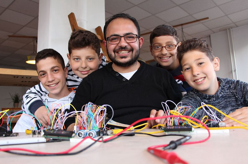 Syrian refugee Asem Hasna and students at his class in Berlin
