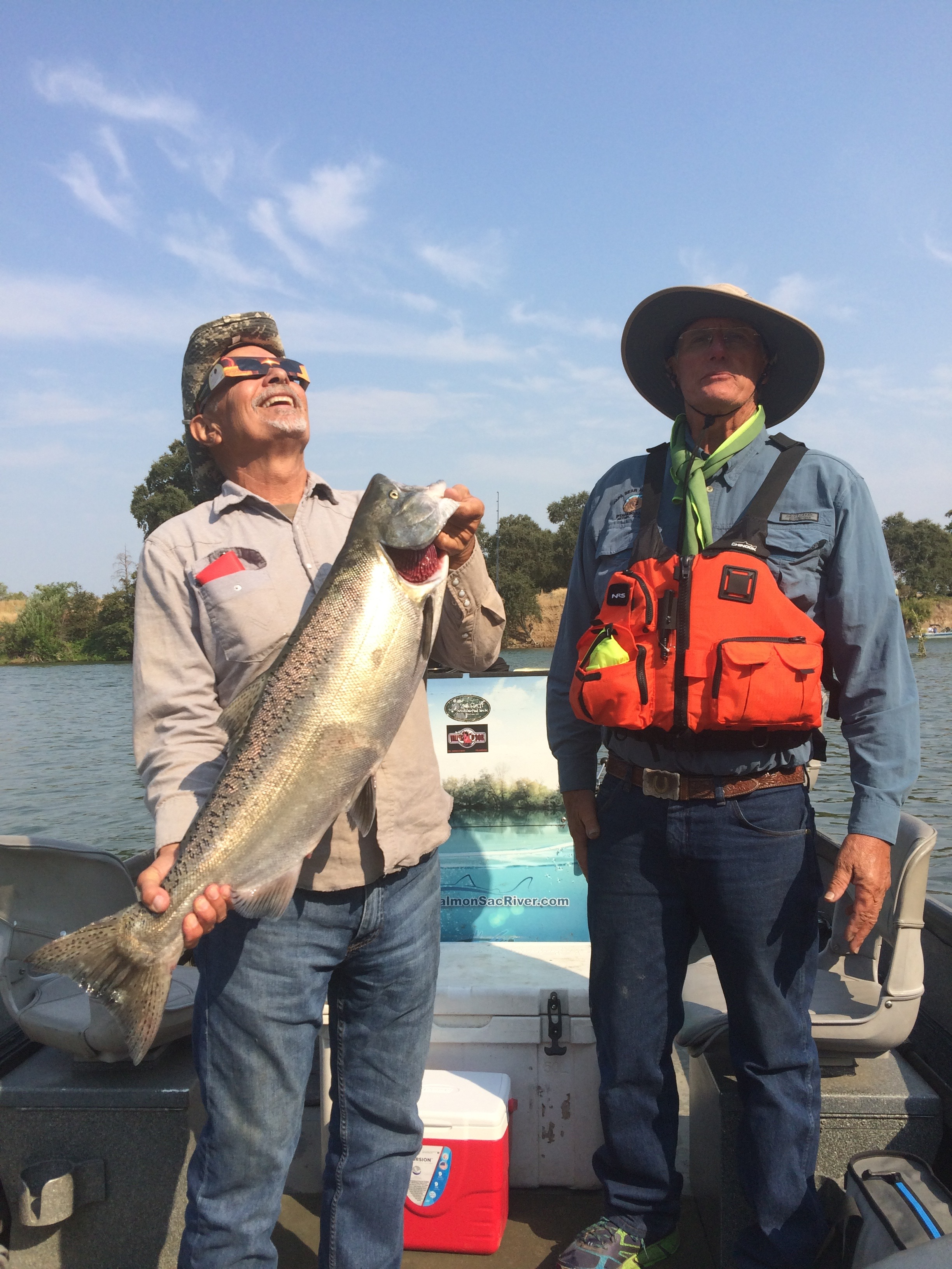 Clients of Mike's Guide Service have their picture taken with a dime bright king salmon they caught at the Outlet Hole during last weeks solar eclipse. Sacramento River Salmon Fishing Guide Mike Rasmussen took the solar eclipse photo of the duo as the moon was already a sliver into the sun.