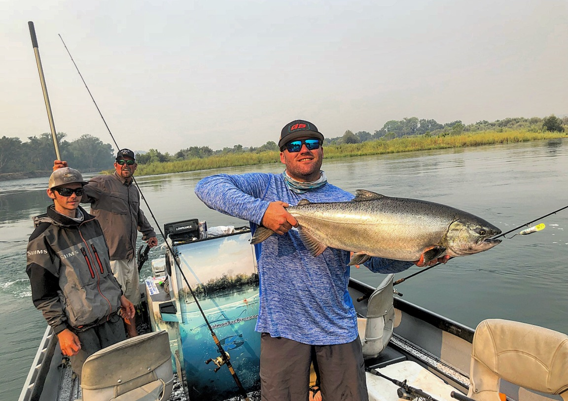 Salmonsacriver.com  guest James Rathjen holds the last chinook salmon of the day for fishing guide Mike Rasmussen and Ryan Tripp, who teamed up for some fast, fun action on opening day at the Barge Hole on the Sacramento River. Photo credits to Christopher Tocatlian.