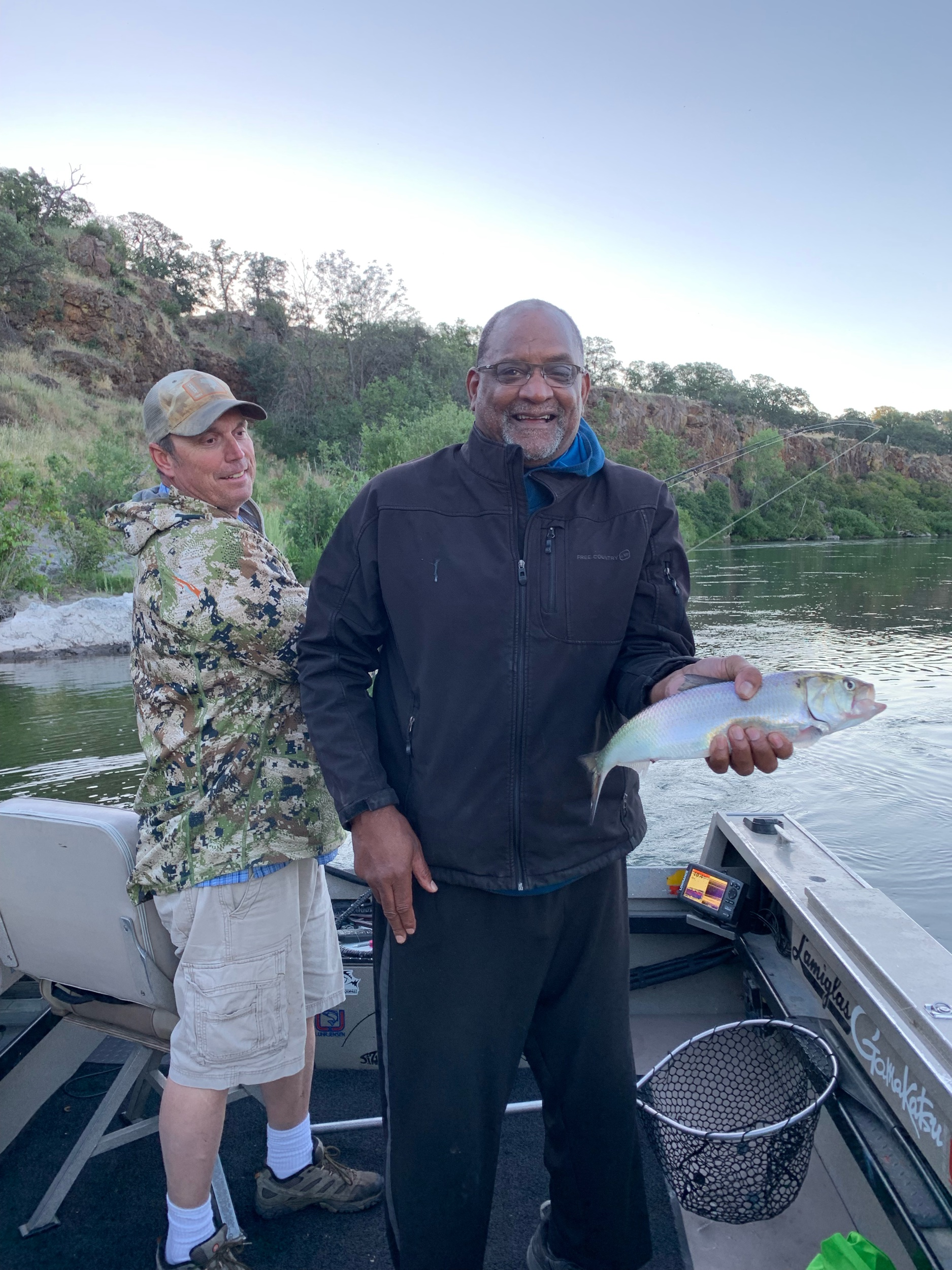 Fishing Guide Dave Jacobs  tel:530 646-9110  of  salmonsacriver.com  watches as client Bruce Jenkins gets his picture taken by fishing guide Mike Rasmussen. American Shad fishing on the Sacramento River has been red hot this week. June 21, 2019