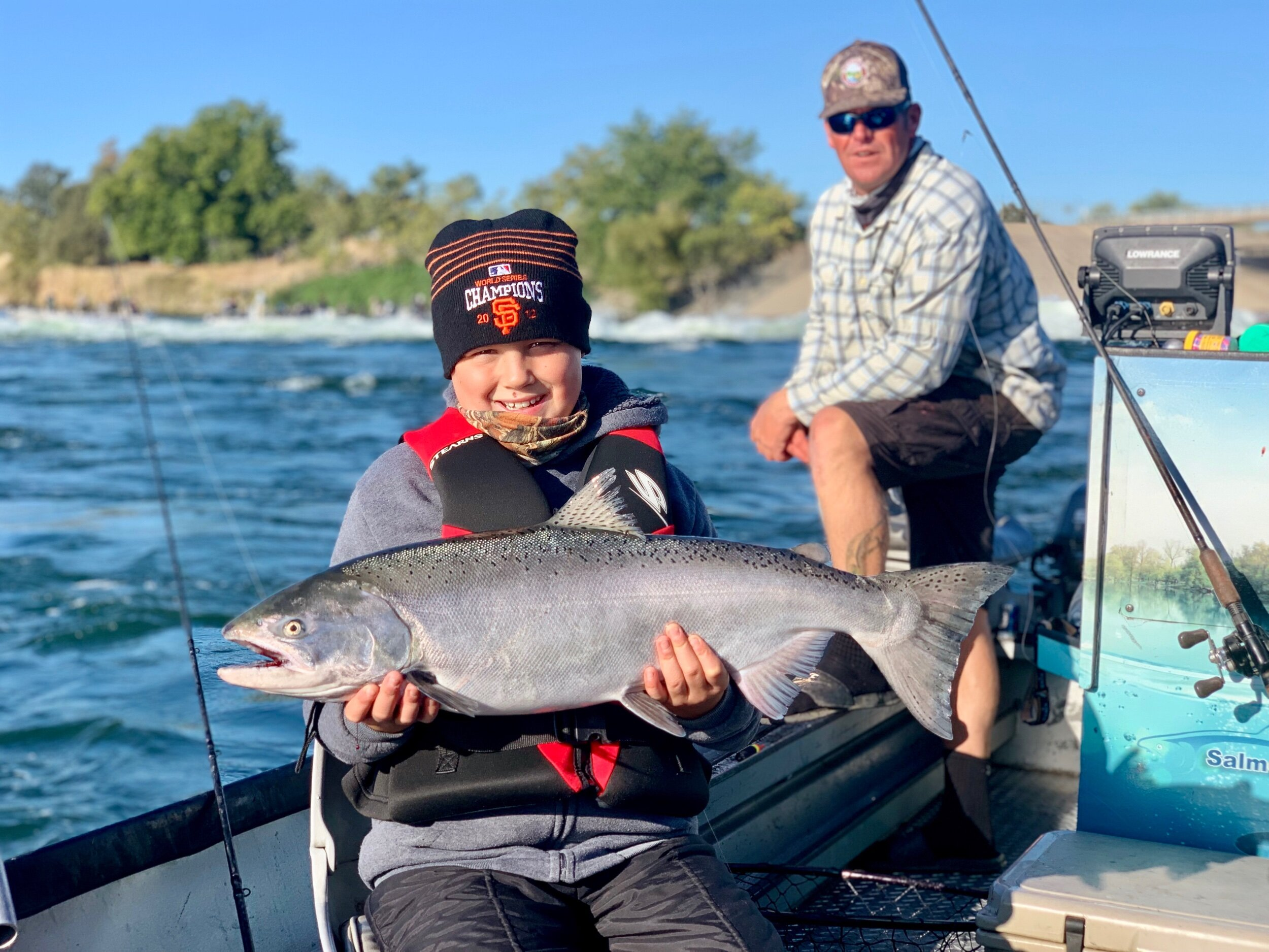A happy young man holding his first ever king salmon he caught on the Feather River with fishing guide Ryan Tripp.