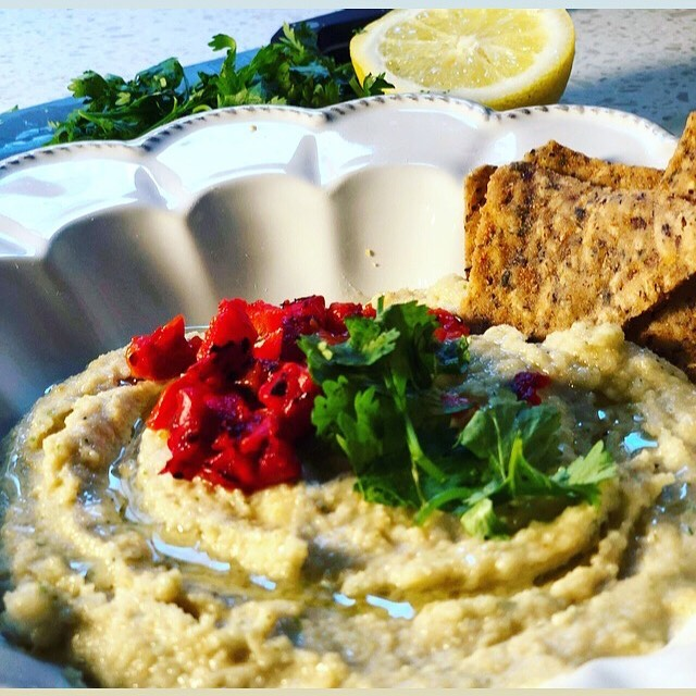 "Peace, family 🤙🏾✌🏾. If you're looking for a more low- carb version of hummus you seriously haaaaave to try this macadamia nut hummus. It's SO easy. This is 1/2 lb salted nuts, 1 squeeze lemon juice, 1/8 cup chopped herbs, 3 garlic cloves, 1/2 tbsp sea salt, 4 tbsp water, and 1 tbsp extra virgin olive oil all thrown into a food processor, and set to ""purée"" for like a minute and a half. Topped with cilantro, EVOO, and roasted red peppers. Served with flax chips. Effing addictive! Happy Sunday."