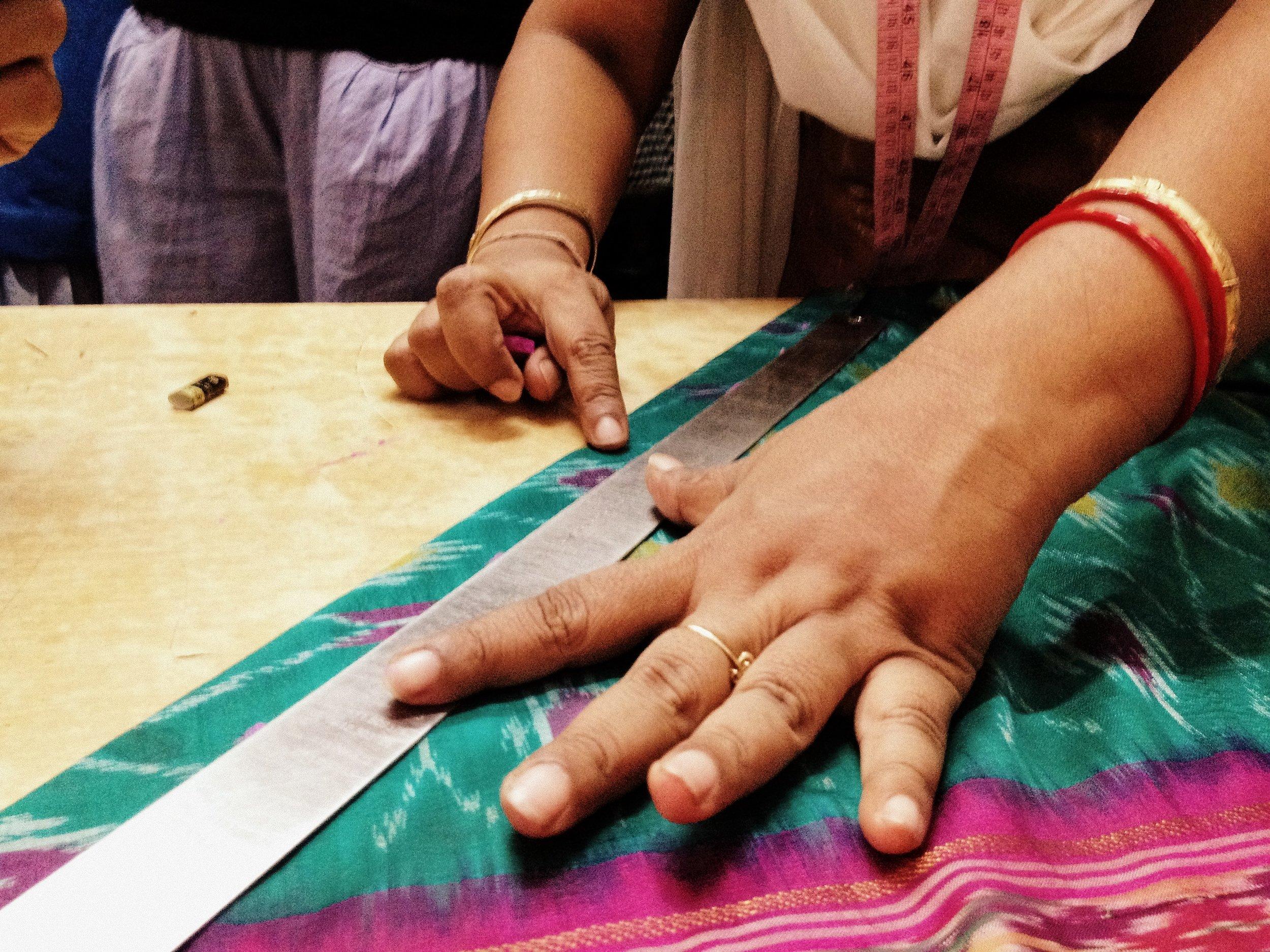 Sari being cut to size to make sari necklaces