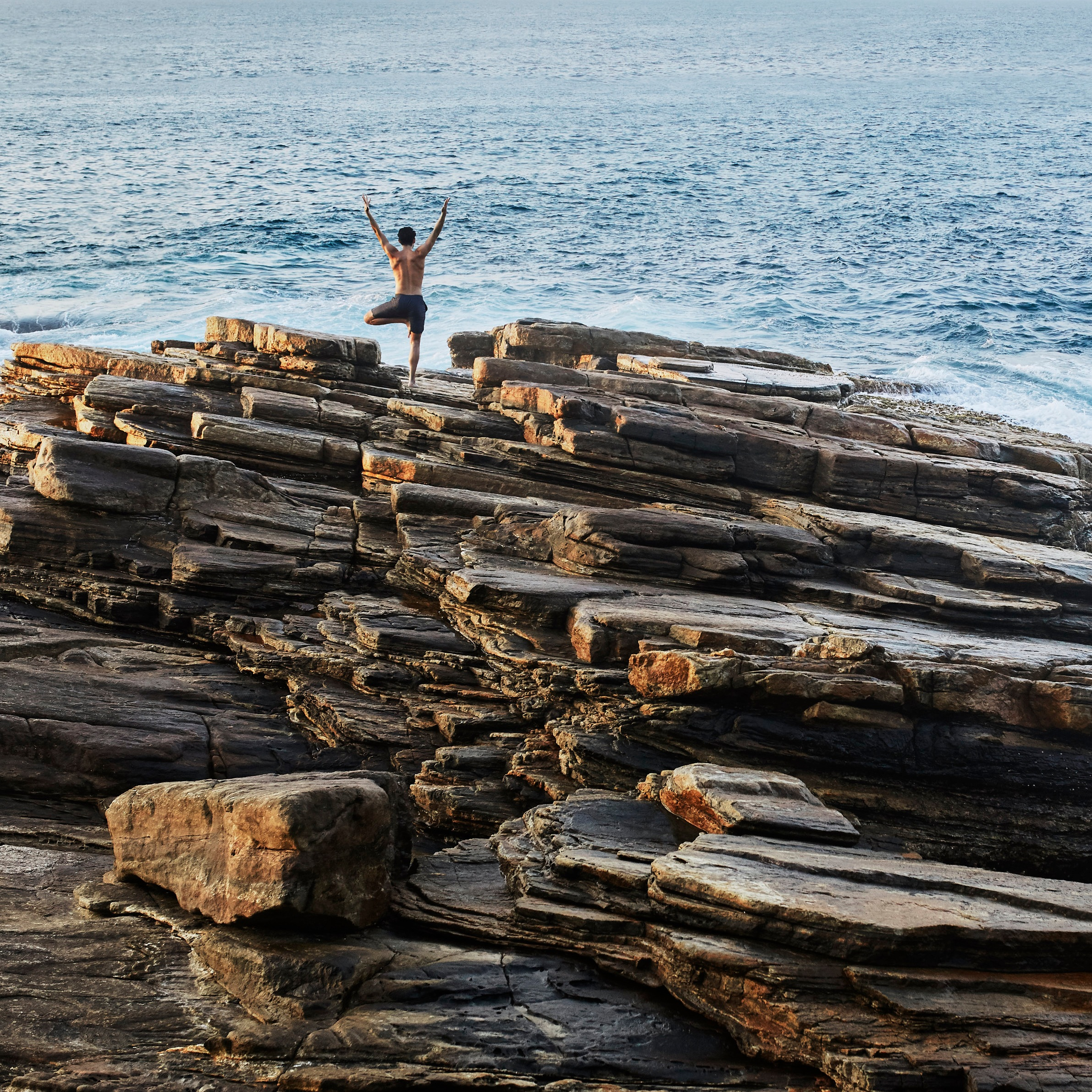 man-doing-yoga-by-ocean