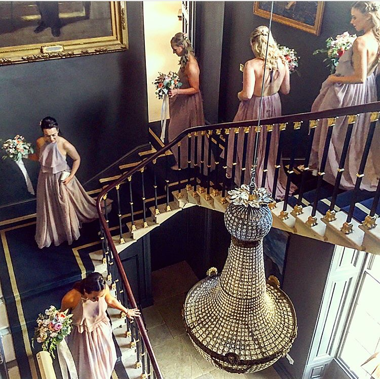 Olivia's bridesmaids making their grand entrance wearing  Olympia in Smoked Orchid gowns .