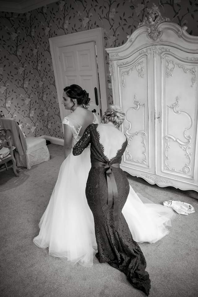 Danielle getting a helping had from bridesmaid Becky wearing our Alara gown in Roseberry -  Photo Ashton Photography