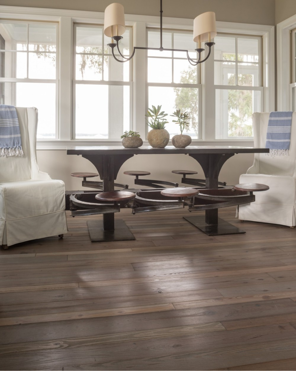 Multiple seating areas, including this wood-and-iron trestle table, accommodate intimate family dinners and big parties with equal success.