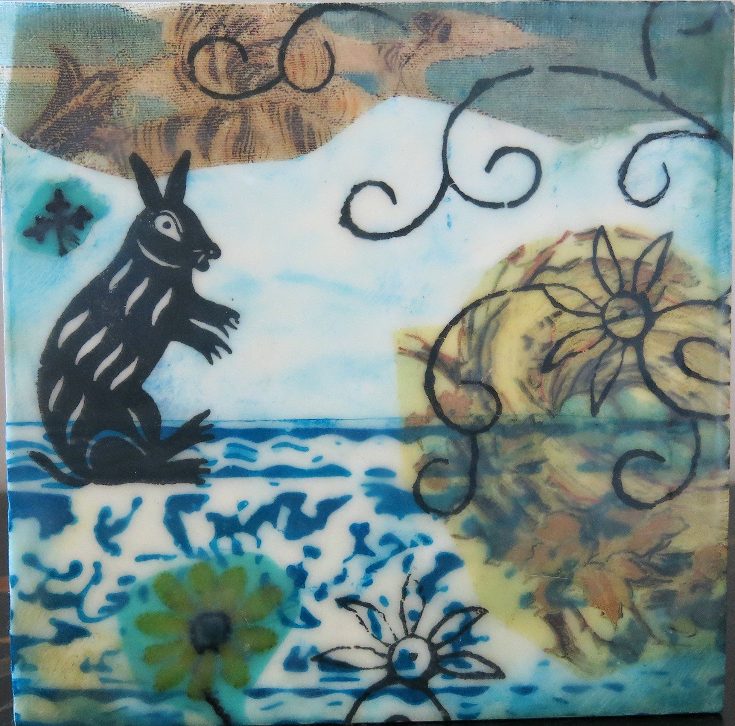 The blue border at the bottom is made by stamping beeswax on paper, painting & ironing out the wax. All of the black designs & rabbit are printed on the surface, then fused with a layer of encaustic medium and heat.