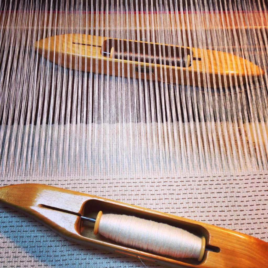 The lighter threads are ground cloth, and the darker are pattern threads that will be gathered.
