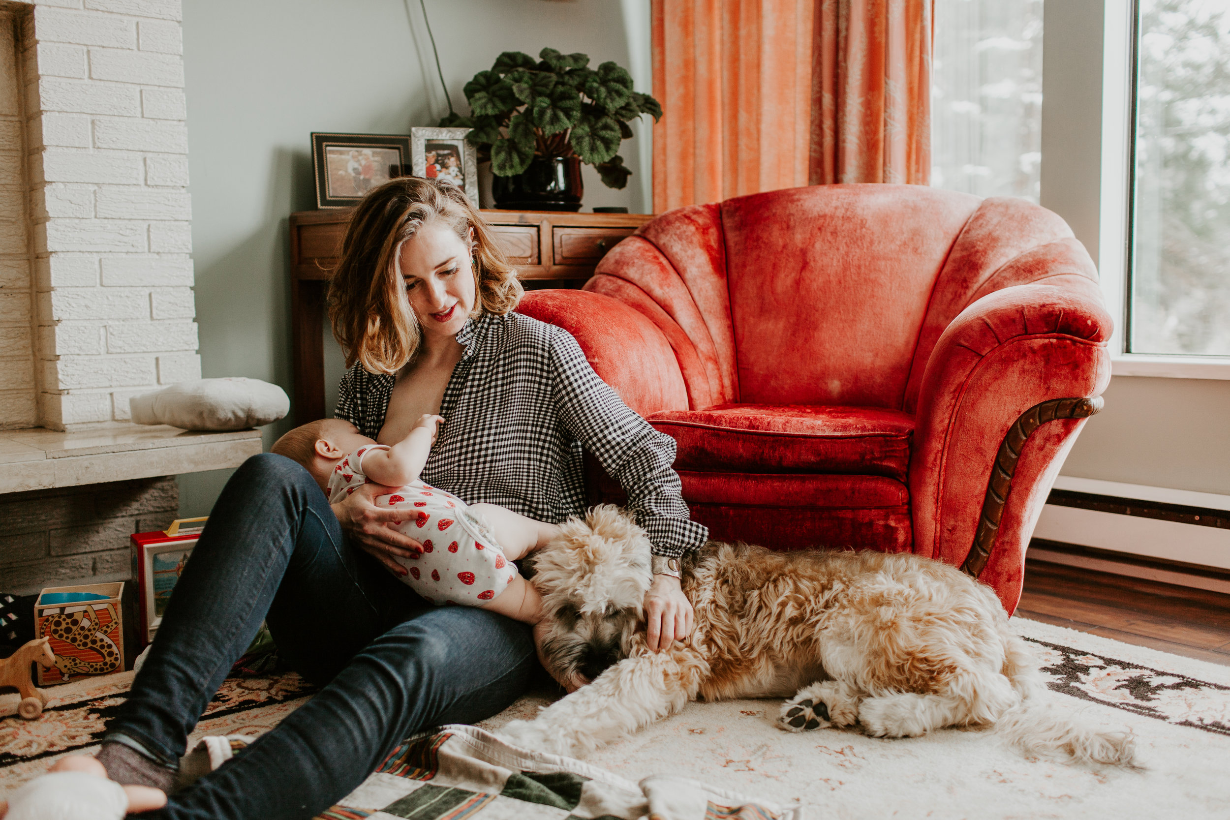 Beautiful mom breastfeeding in living room and snuggled up with her dog.jpg