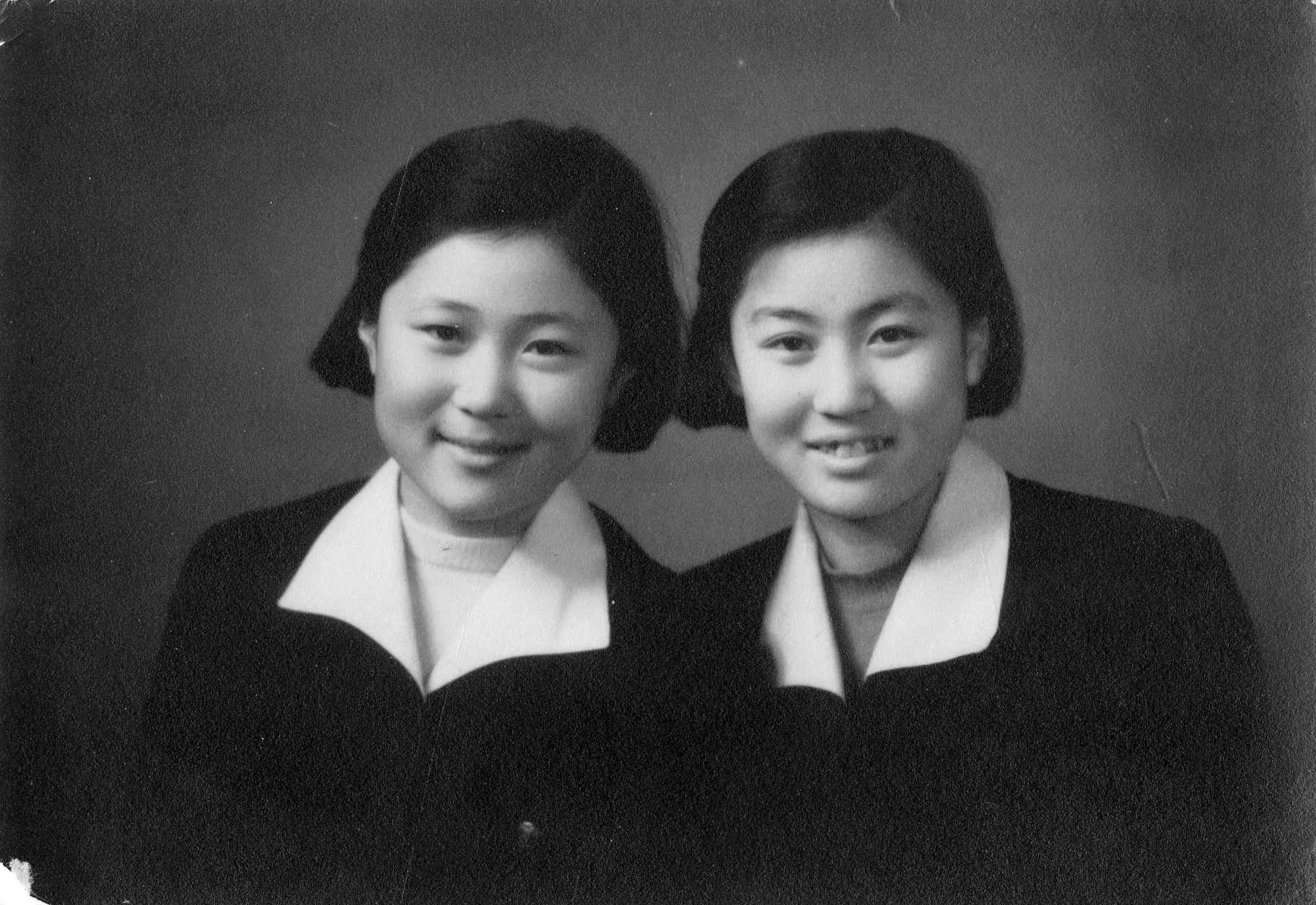 With her sister, in their school uniforms, 1950s