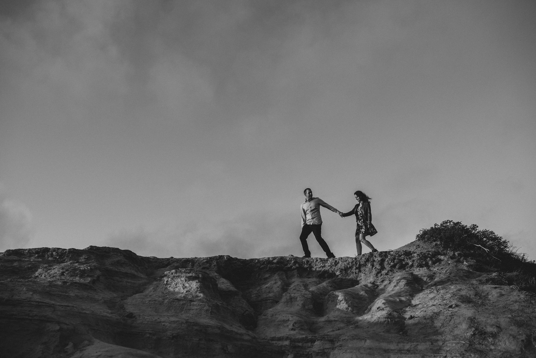 A man leads his fiancé across the jagged ridge line high above the cliffs at Torrey Pines State Reserve.