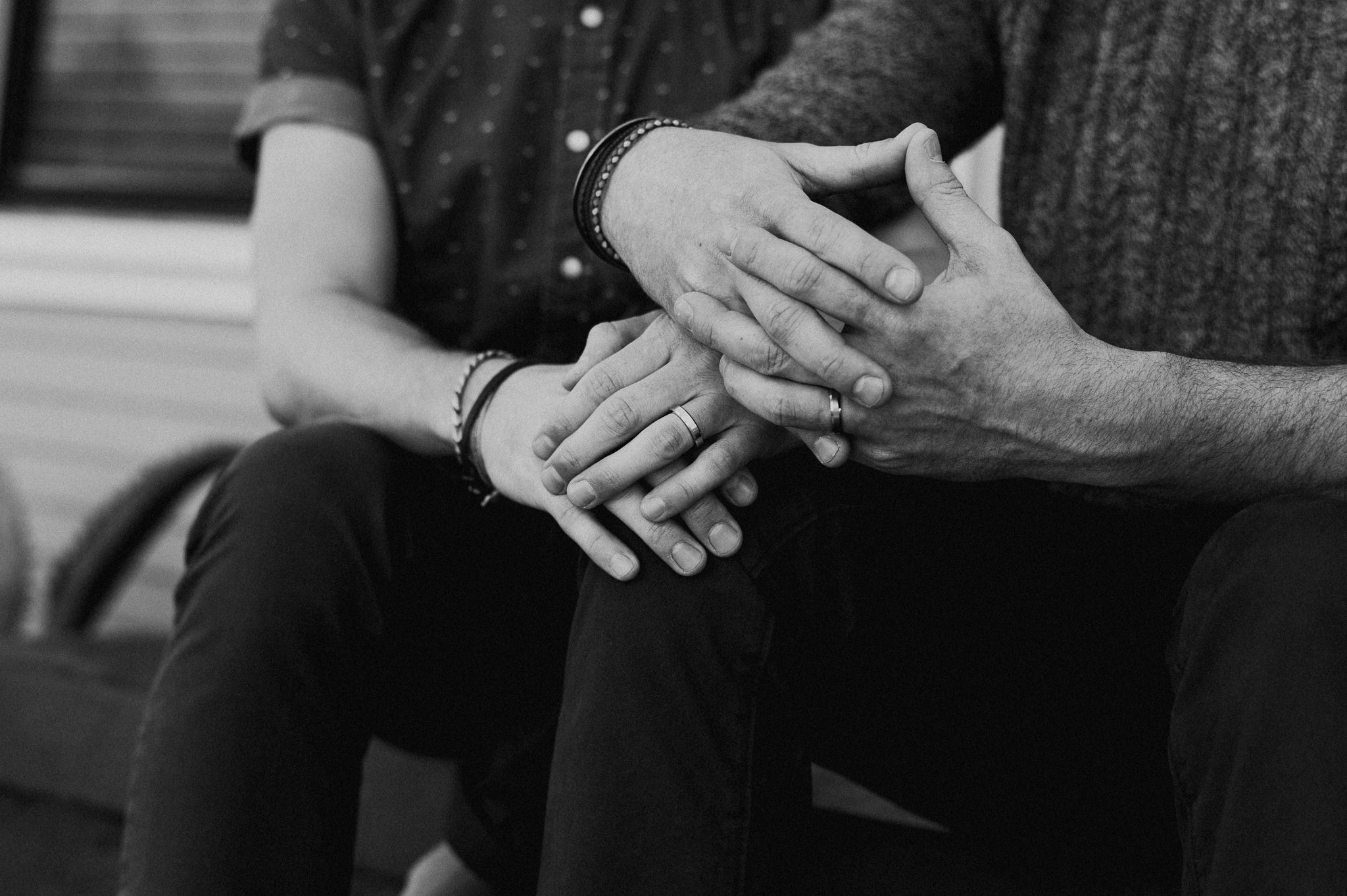 A man and his husband sitting on a stoop with their hands overlapping and showing off their wedding rings.