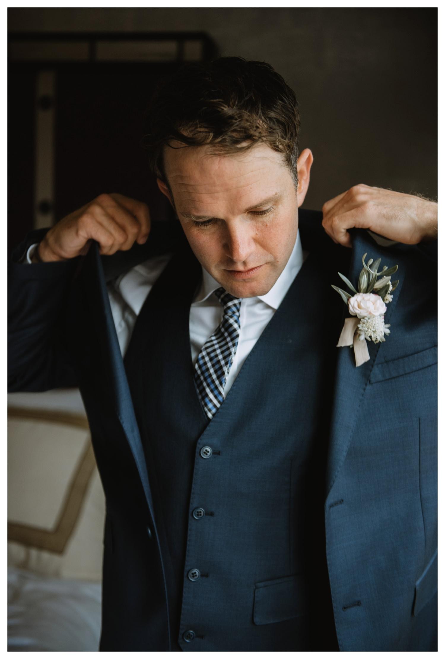A groom adjusts his jacket on his wedding day