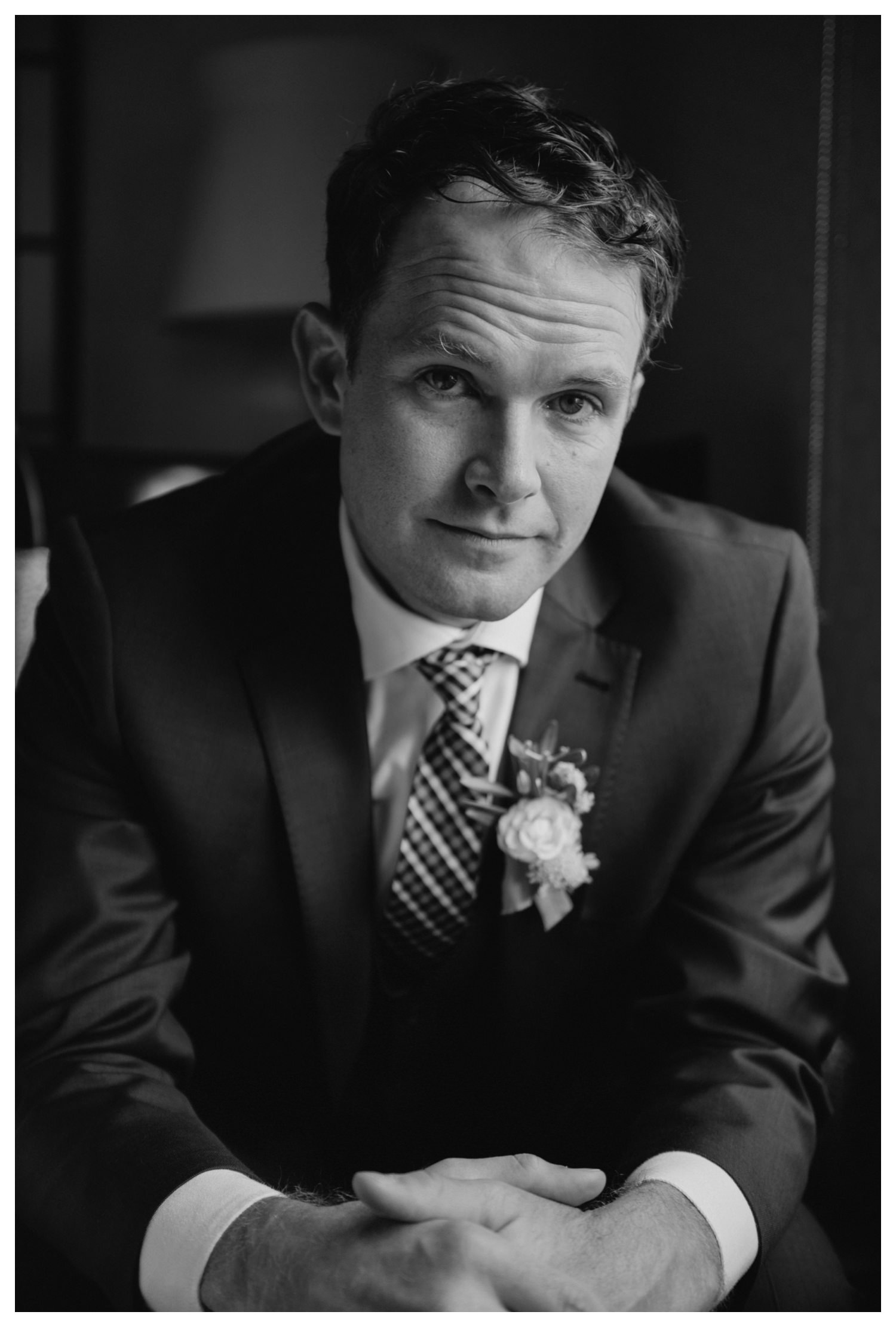 a groom stares calmly into the camera on his wedding day