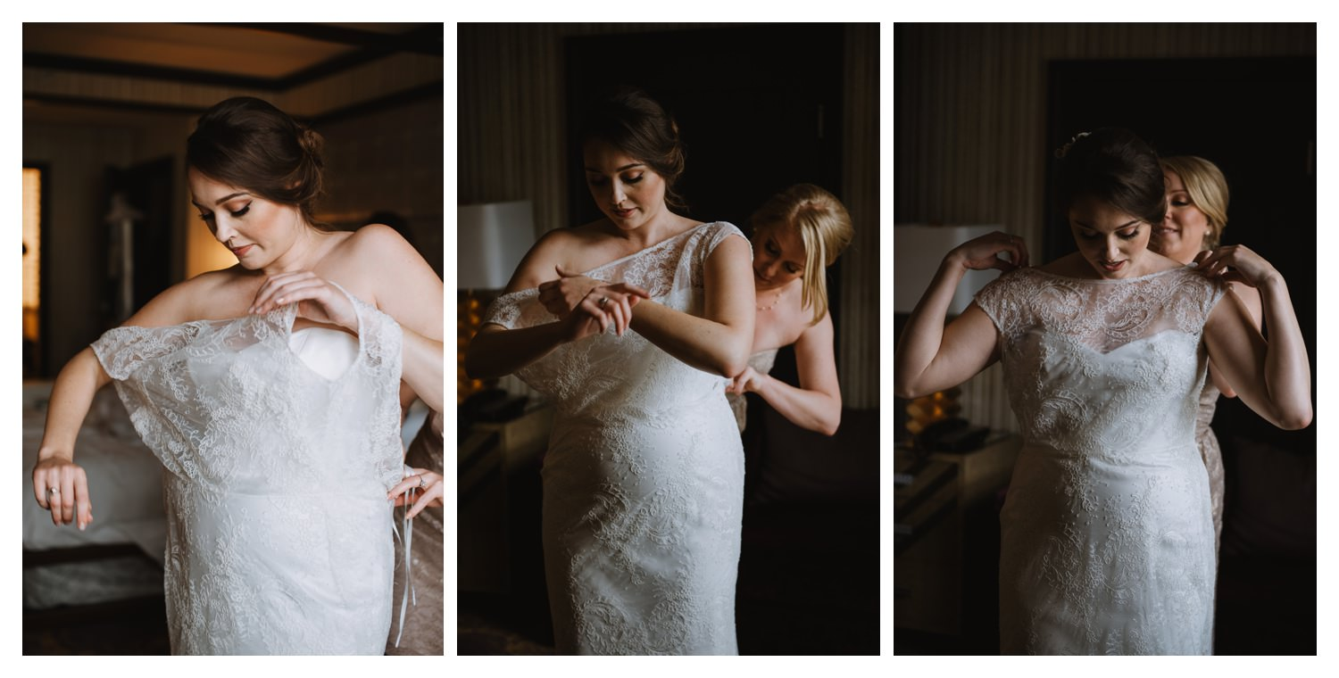 A beautiful bride is helped into her wedding dress