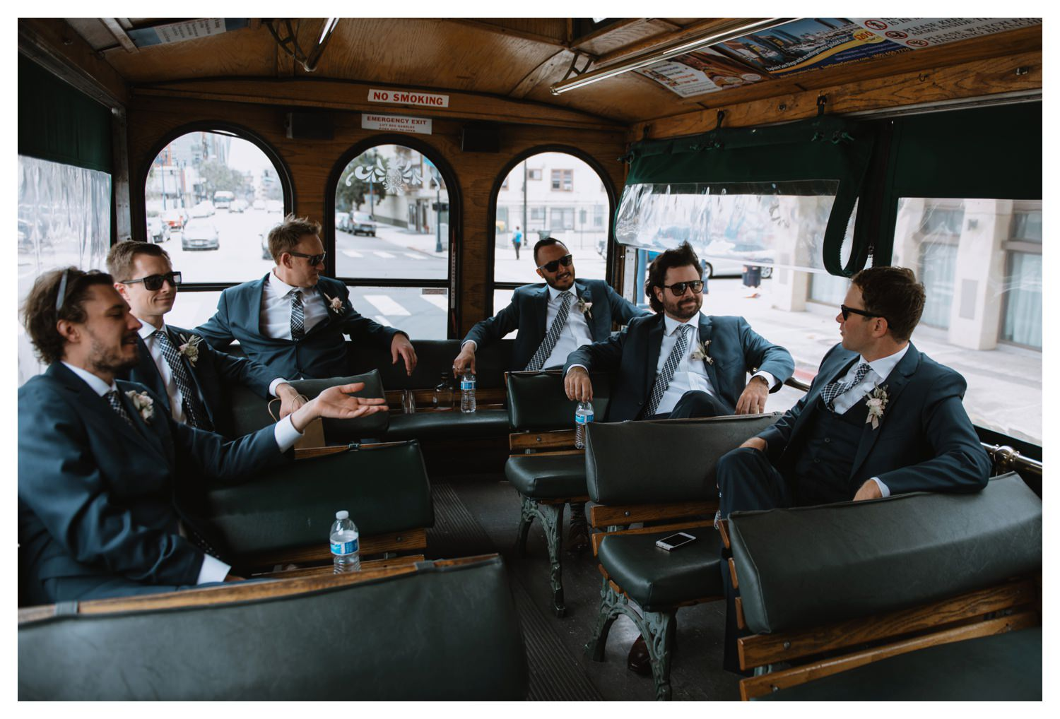 Groomsmen laugh on a bus on their way to the wedding