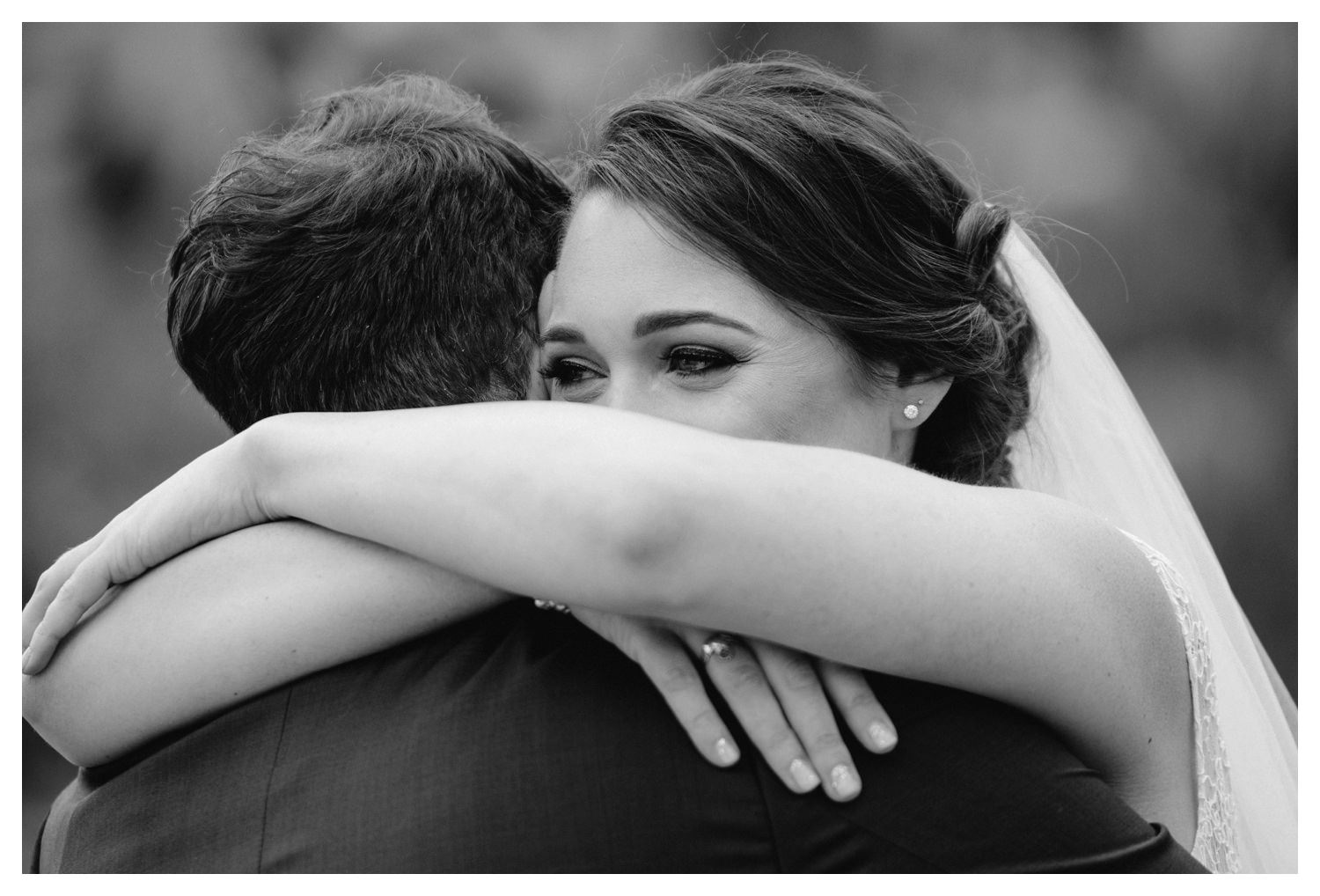 a bride and groom embrace on their wedding day.