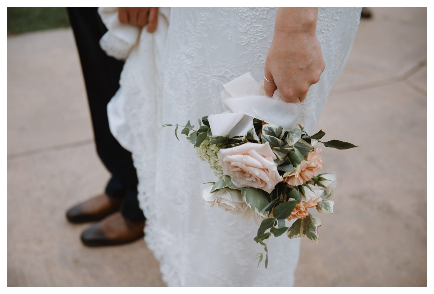 A gorgeous wedding bouquet hangs nonchalantly at the brides side.