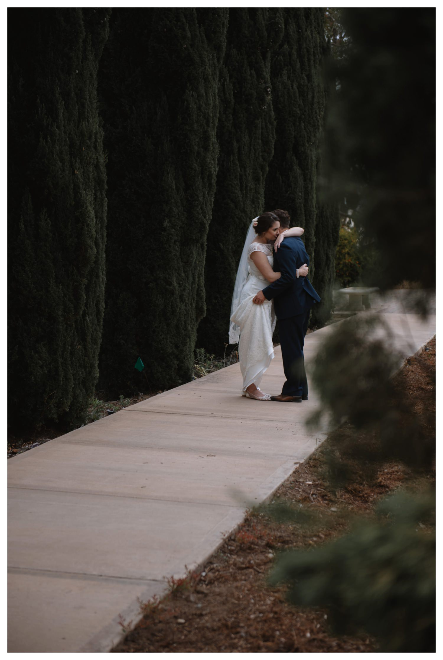 A wedding couple embrace at Balboa Park in San Diego