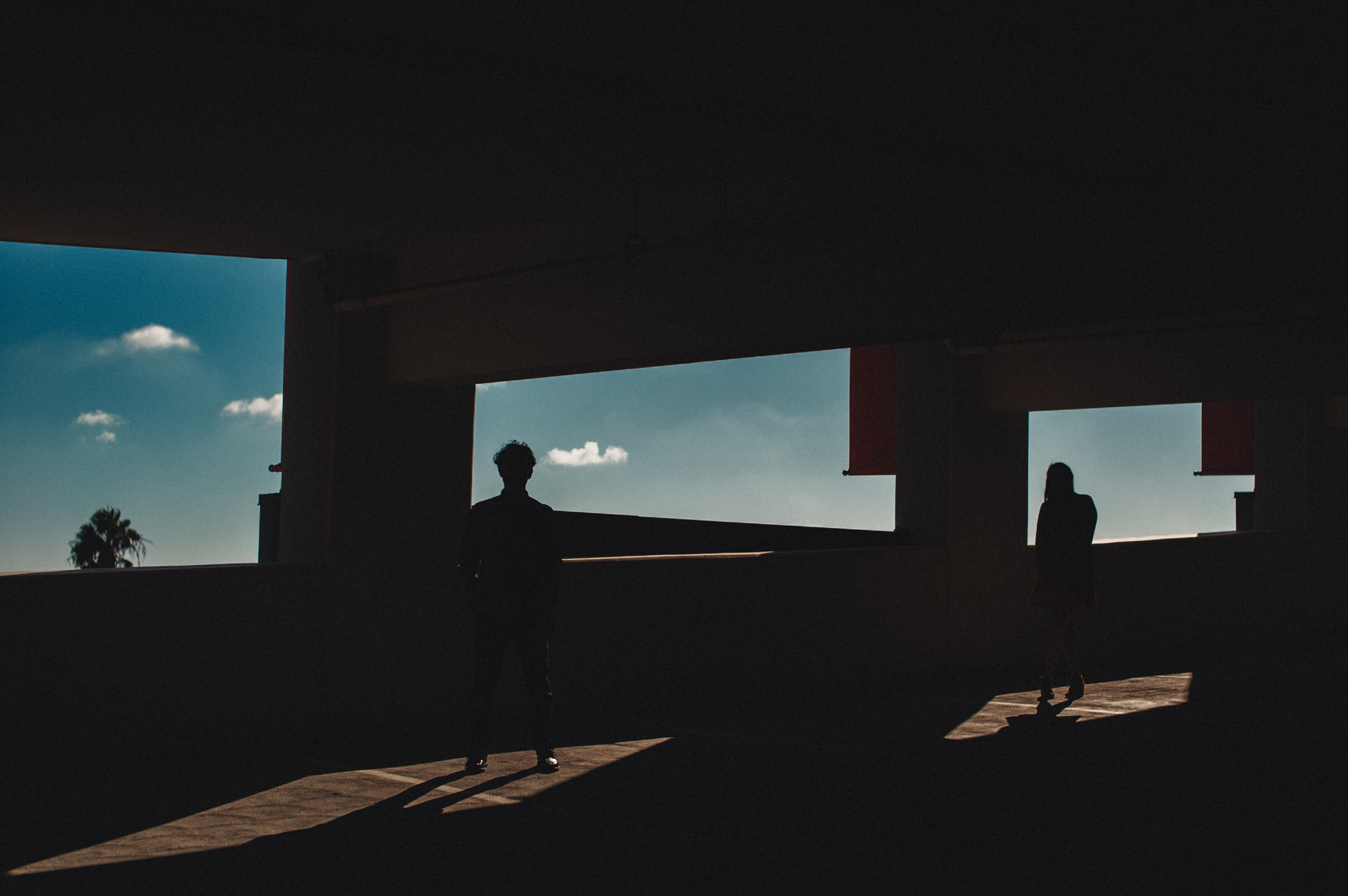 A man and his fiancé are silhouetted in a parking garage as the bright light from  outside backlights them.