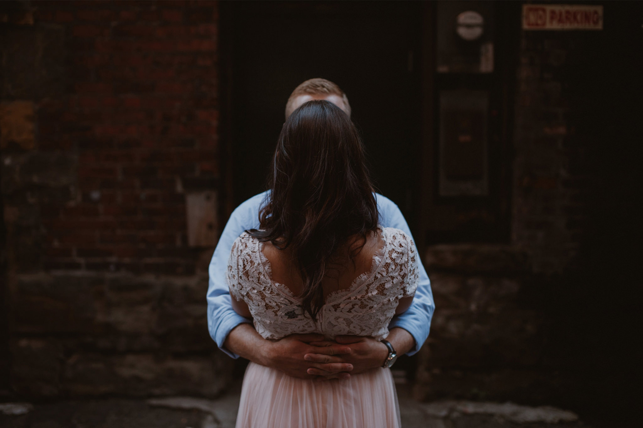 An engaged couple embrace in a Seattle alley