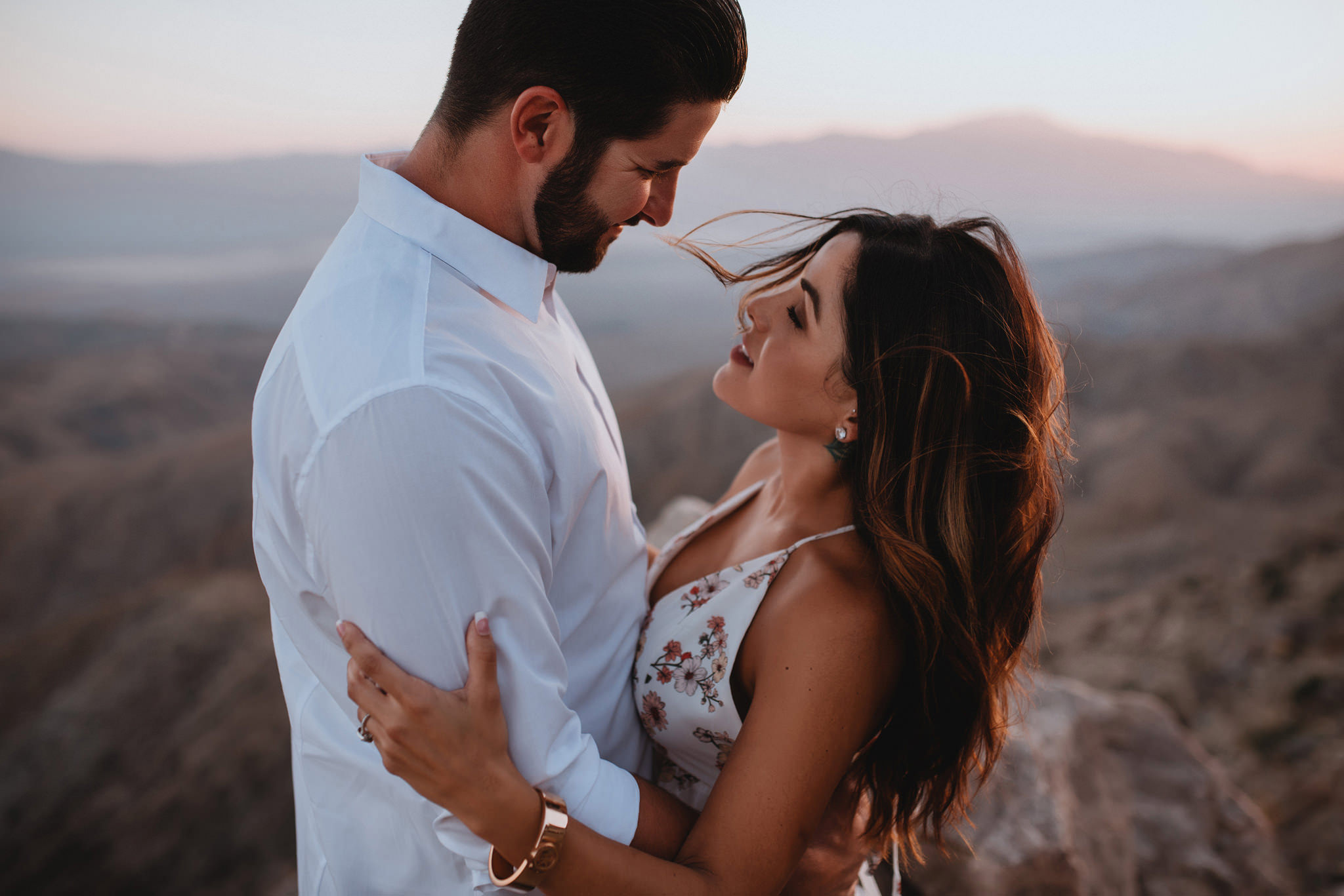 An engaged couple standing on a cliff as the wind blows in Joshua Tree