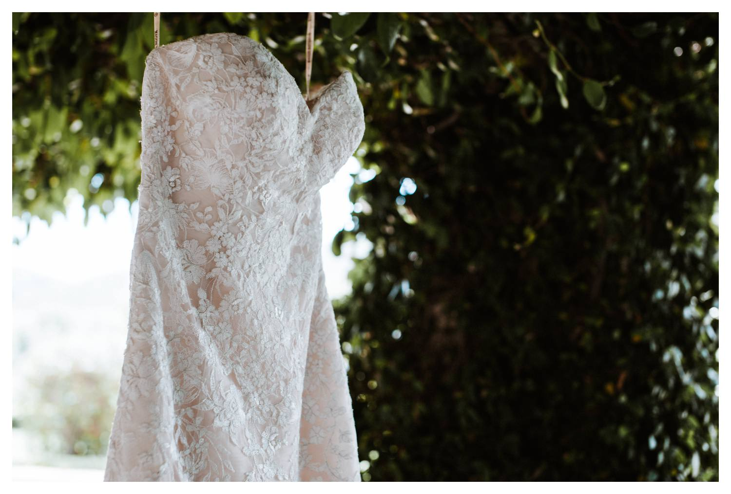 Details of a wedding dress against a green ivy wall