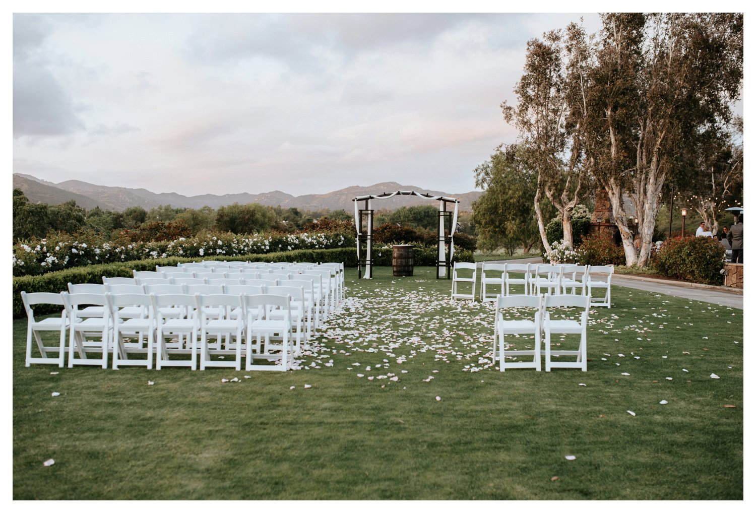 Flower pedals strewn across a lawn after a beautiful wedding ceremony at Twin Oaks Golf Course.