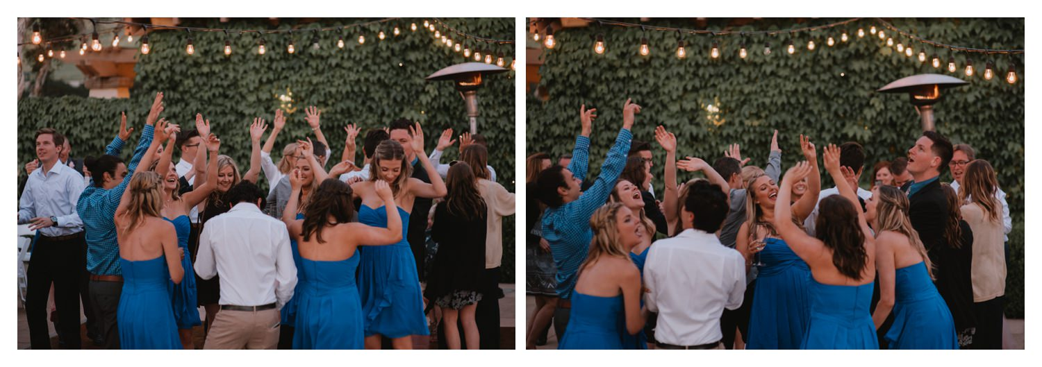 Wedding attendees throw their hands up on the dance floor.