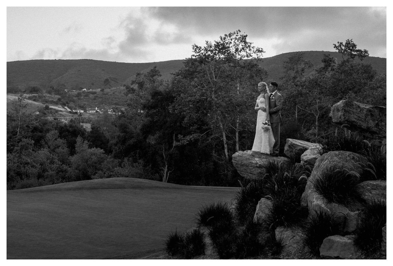 A bride and groom pose a top rocks at Twin Oaks Golf Course in San Marcos, CA.