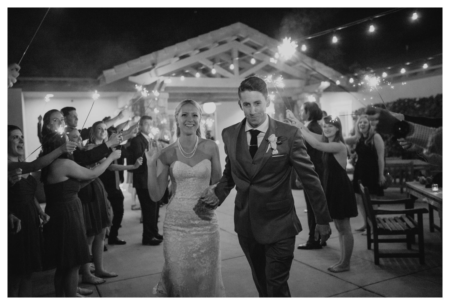 A bride and groom make their grand exit  under the fire light of sparklers.