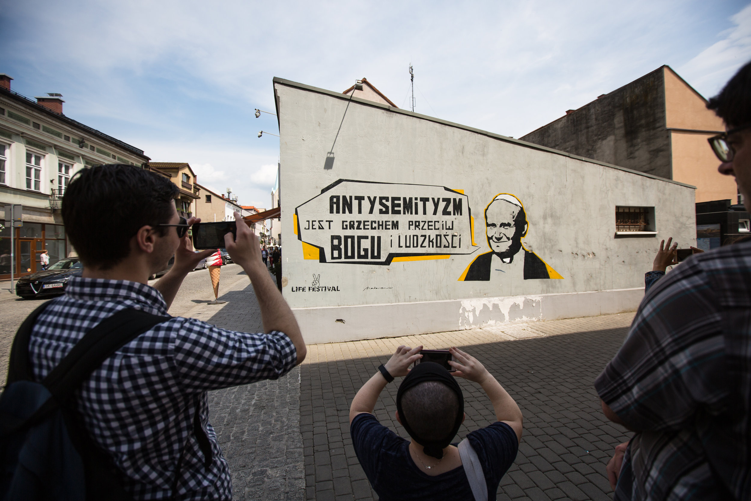 """Participants photograph a mural with an image of the Pope and the caption """"Antisemitism is a sin against man and humanity"""" on May 27, 2019 in Oswiecim, Poland. (Photo by Elan Kawesch/TRTN)"""
