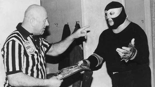 NWA referee and president bob Geigle takes the NWA World title away from the midnight rider (Dusty Rhodes)