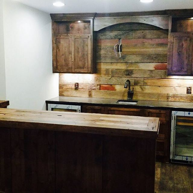 Basement bar with reclaimed wood bar top and accent wall.