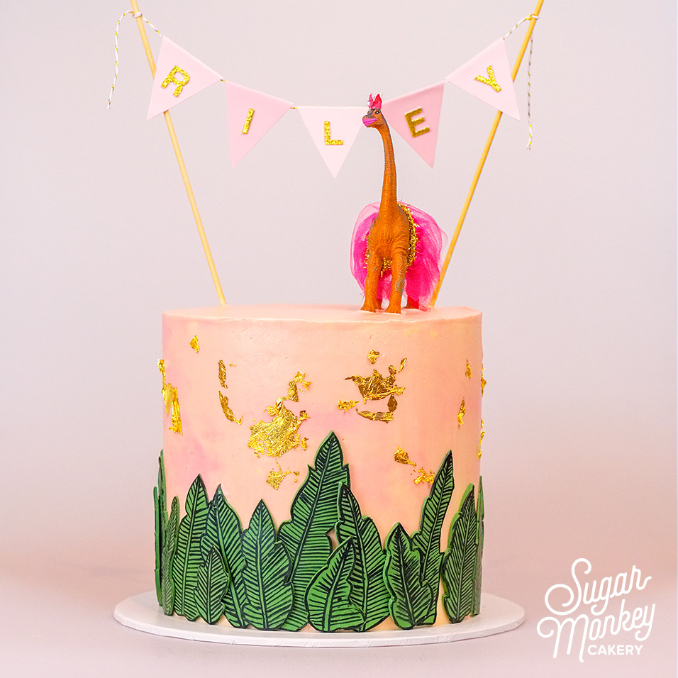 Double barrel cake with hand painted fondant leaves and dinosaur topper