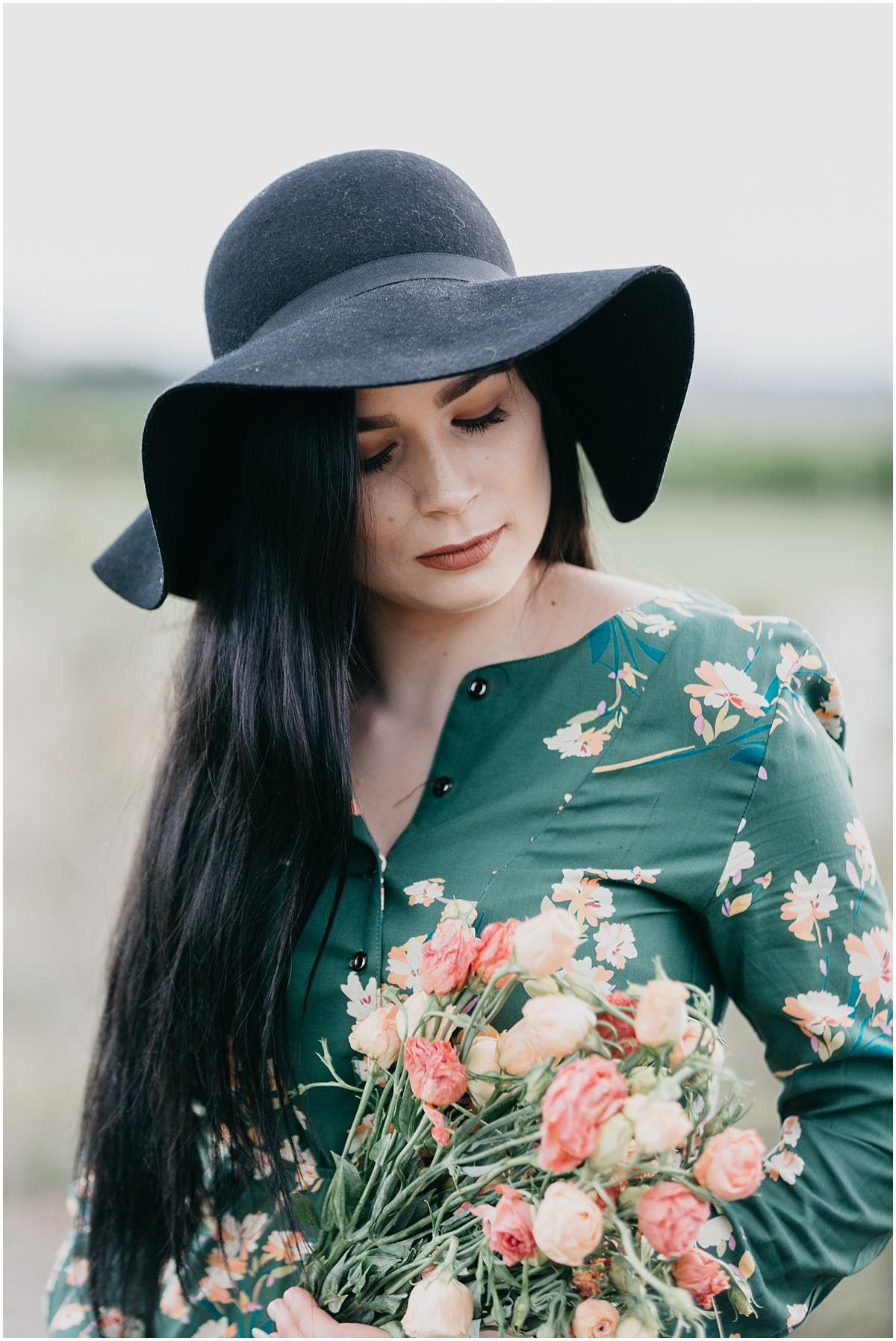 Woman in black hat wearing green dress holding bouquet of flowers